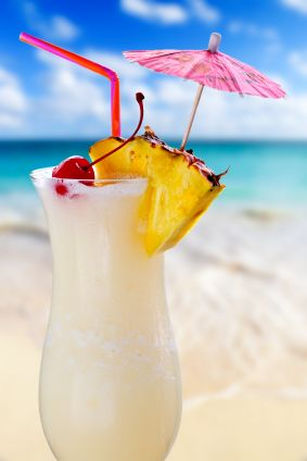 Pina colada drink in cocktail glass with tropical beach in background